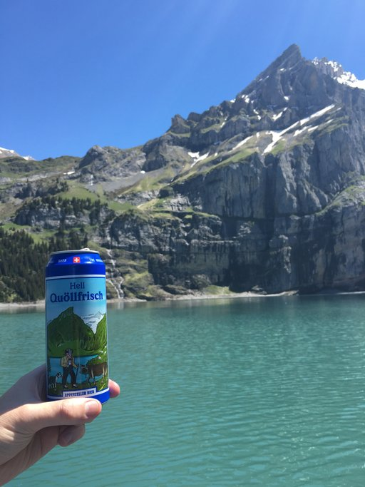 Beer can with a mountain on its label in front of a real mountain that looks exactly like it